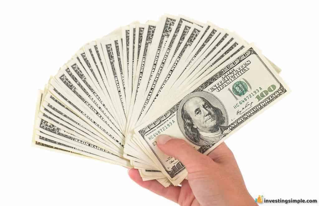 A person holding money that they earned through residual income.